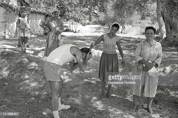Girl pouring water on the head of a Greek torchbearer Greece August 1960