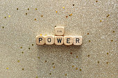 """""""GIRL POWER"""" printed on wood dice against gold glitter background."""