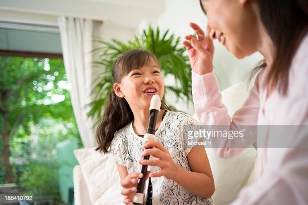 A girl  practices flute with her grandma