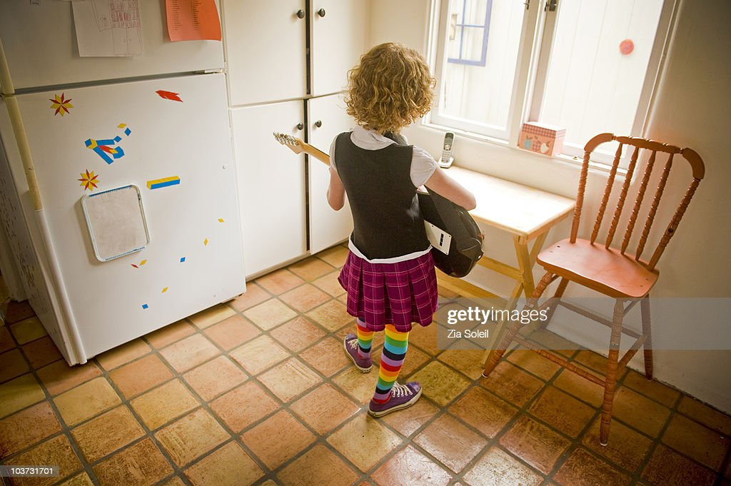 girl practicing electric guitar in empty kitchen : Stock Photo