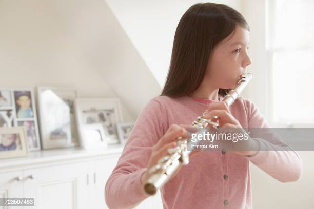 Girl practicing flute in living room