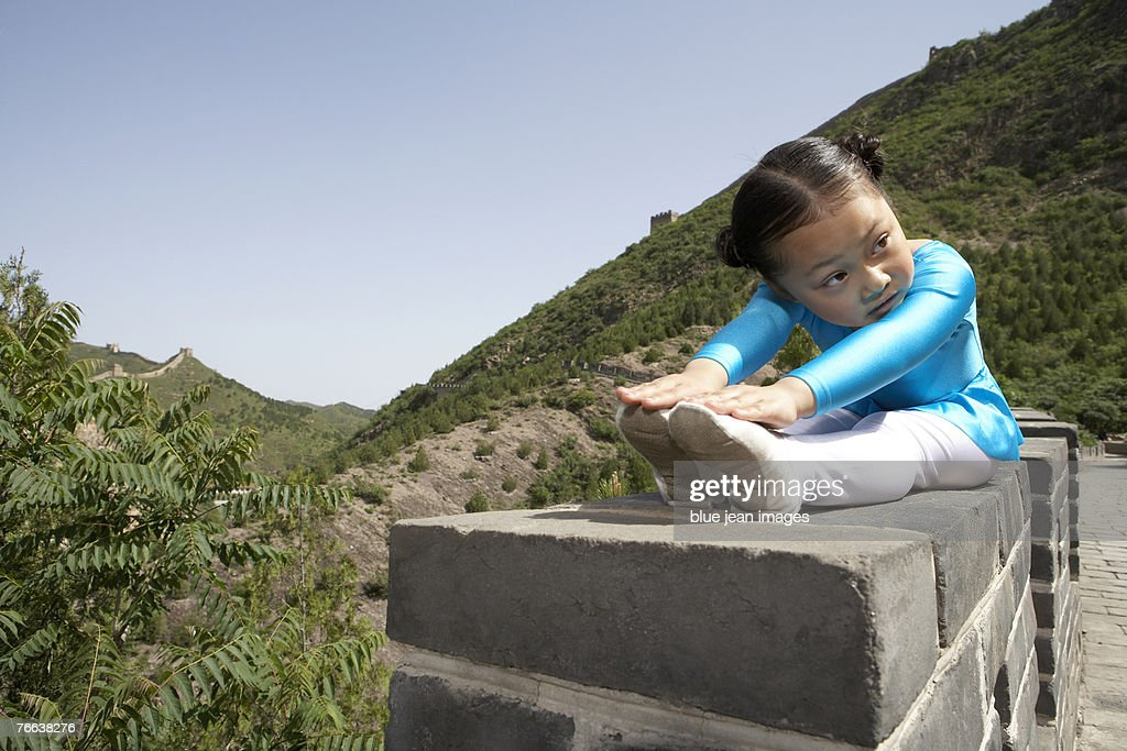 A girl practicing gymnastics on the Great Wall of China. : Stock Photo