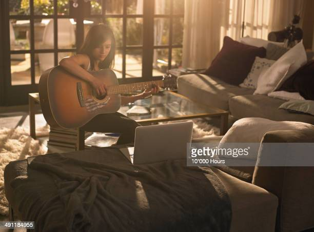 A girl practising the guitar, looking at a laptop