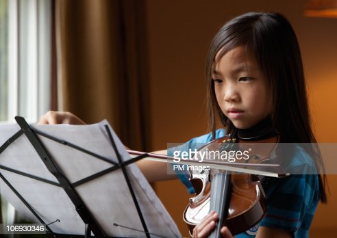 Girl practising violin : Stock Photo