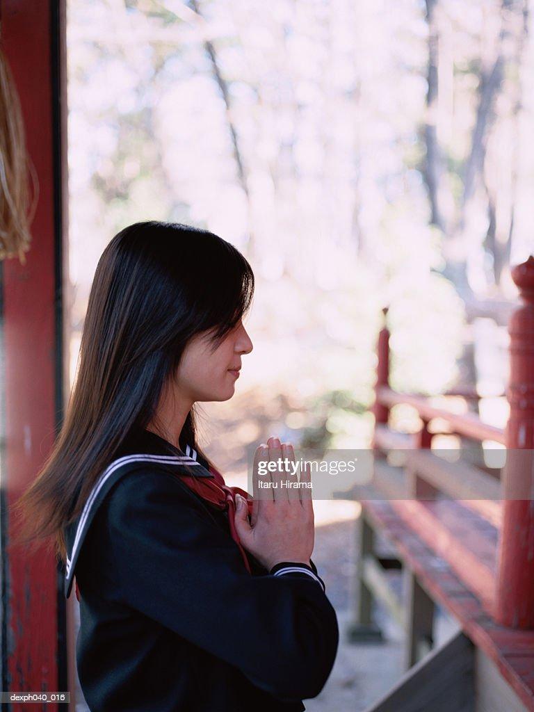 Girl praying outside a shrine