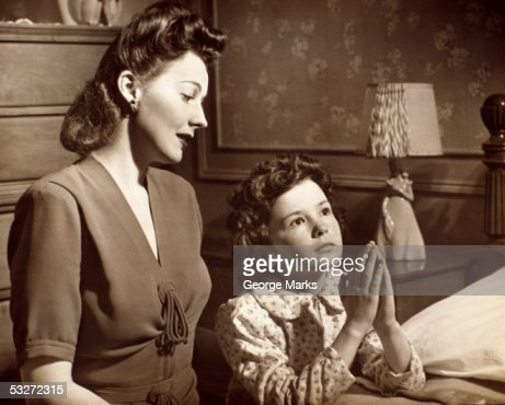 Girl praying with mother : Stock Photo