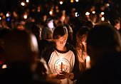 A girl prays during a vigil in Roseburg Oregon on October 1 for ten people killed and seven others wounded in a shooting at a community college in...