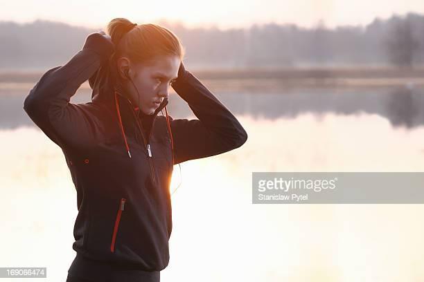 Girl preparing to jogging at morning near a lake