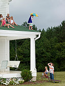Girl (10-11) preparing to jump off roof of house onto small trampoline, with other children watching
