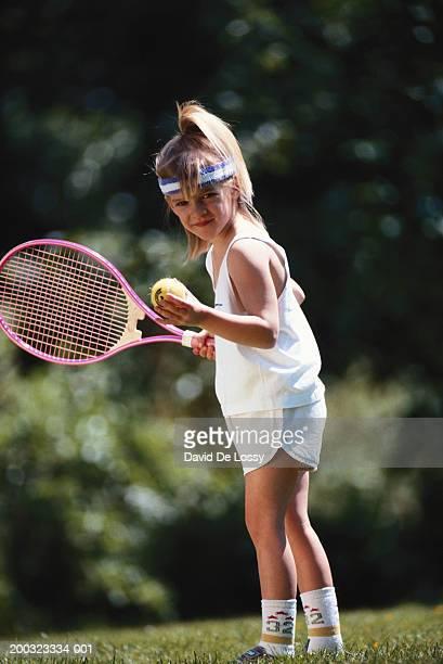Girl (6-7) preparing to serve tennis ball