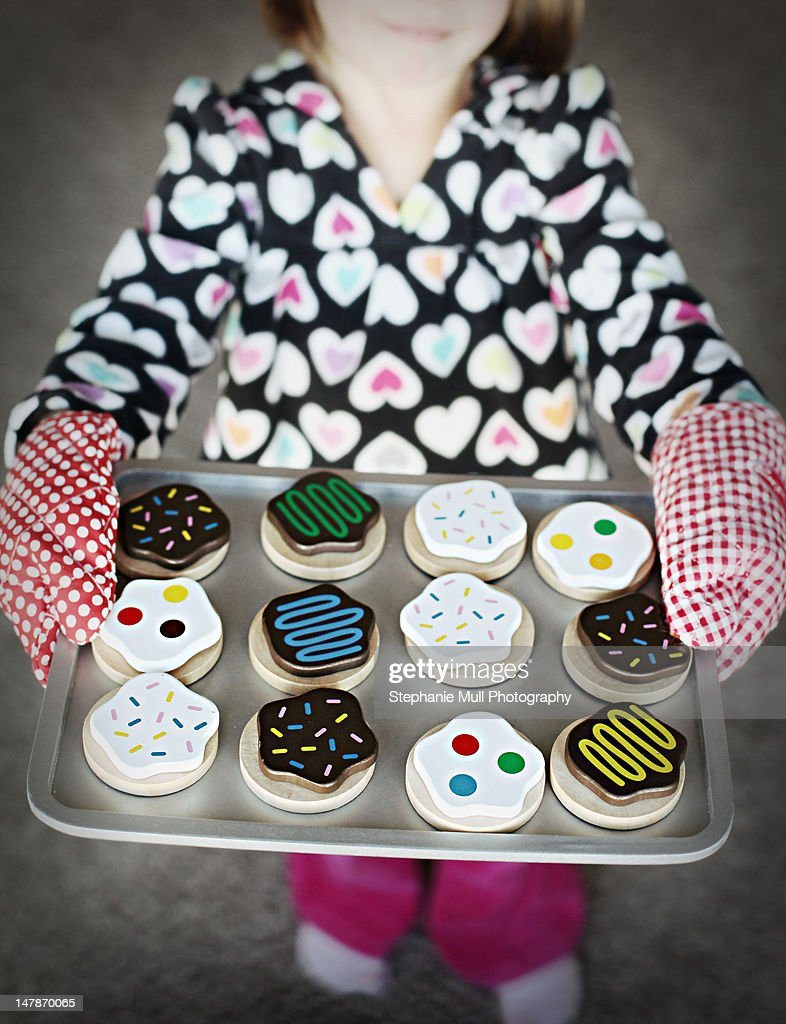 Girl presenting tray of pretend baked cookies : Stock Photo