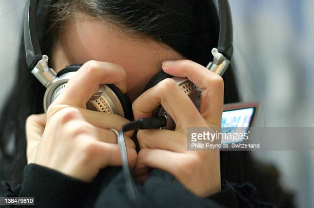 Girl pressing headphones into eyes