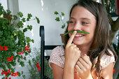girl pretending green bean is a moustache