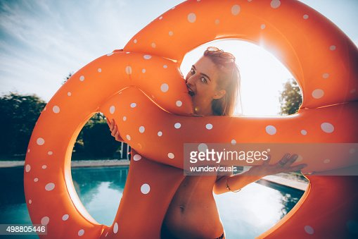 Girl pretending to bite a pretzel shaped pool inflatable