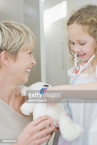 Girl pretending to listen to stuffed animals heartbeat with toy stethoscope : Stock Photo