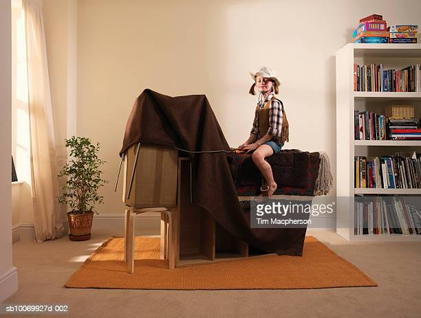 Girl (8-9) pretending to ride horse made from furniture and blanket