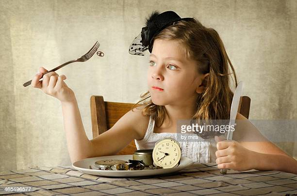 Girl pretends to eat clock, time