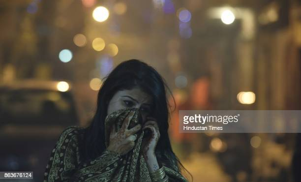 A girl protects her face amid heavy smog due to bursting firecrackers despite the ban imposed by the Supreme Court of India to keep a check on air...