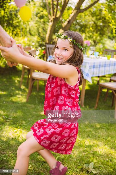 Girl pulling adult's arm in garden