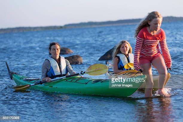 Girl pulling kayaks in sea