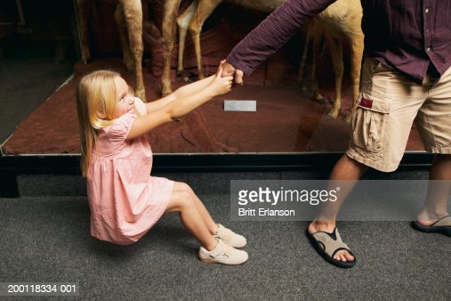 Girl (5-7) pulling on man's hand in museum