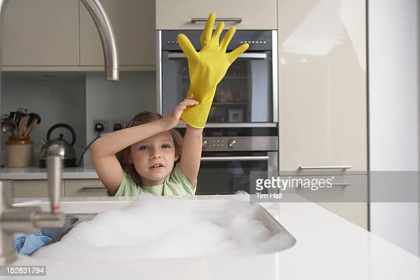 Girl pulling on rubber glove at sink