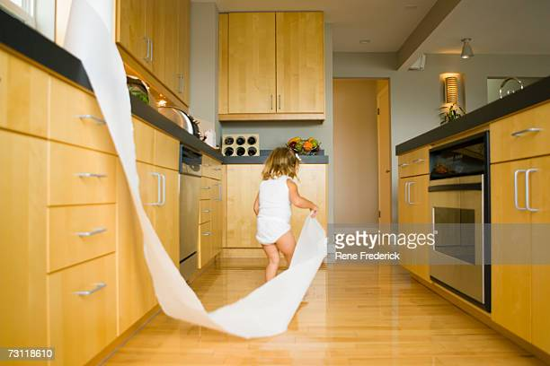Girl (2-4) pulling roll of paper towels across kitchen, rear view