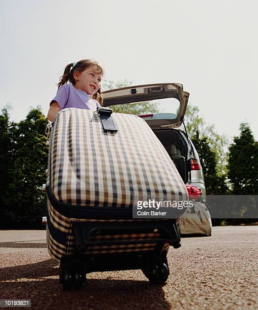Girl (4-6) pulling suitcase towards family car, low angle view