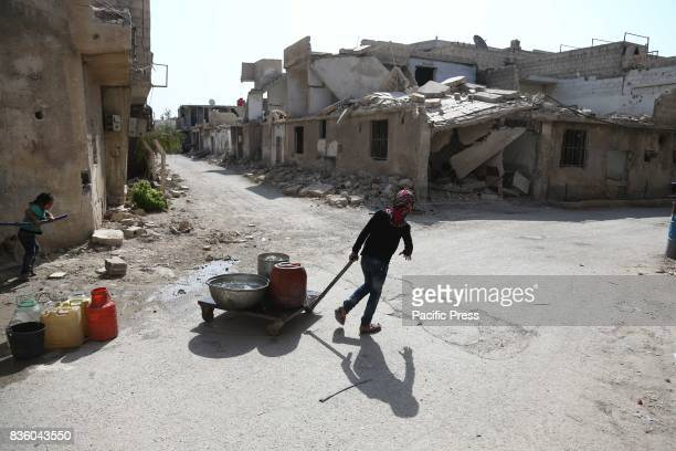 A girl pulls a cart loaded with some pots filled with water in one of the destroyed streets in Zamalka in the eastern Ghouta and the area under the...