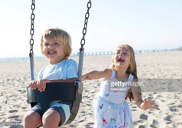 Girl pushing a boy on a swing
