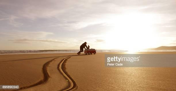Girl pushing toddler in toy car on beach