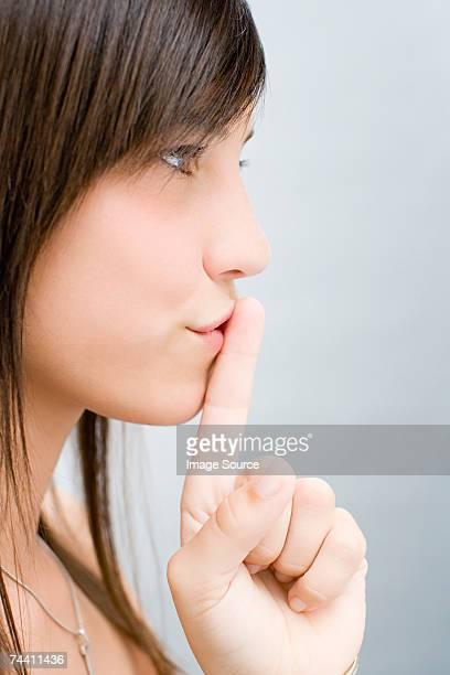 Fille de mettre le doigt sur les lèvres son