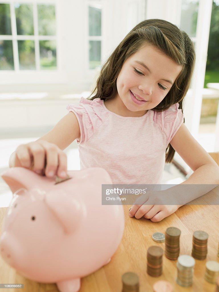 Girl putting coin into piggy bank : Stock Photo