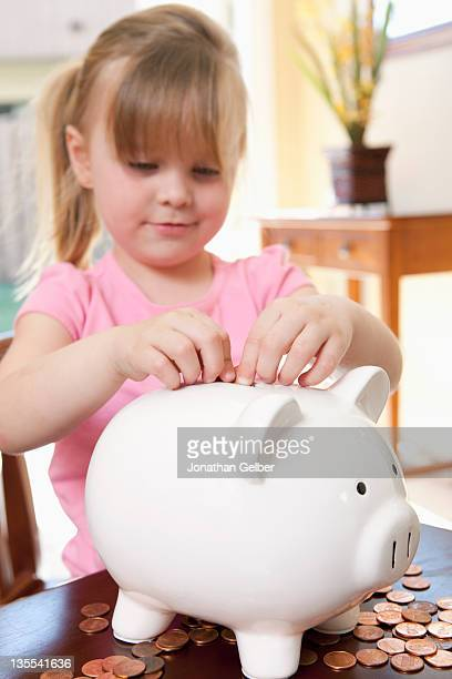 A girl putting coins into a piggy bank