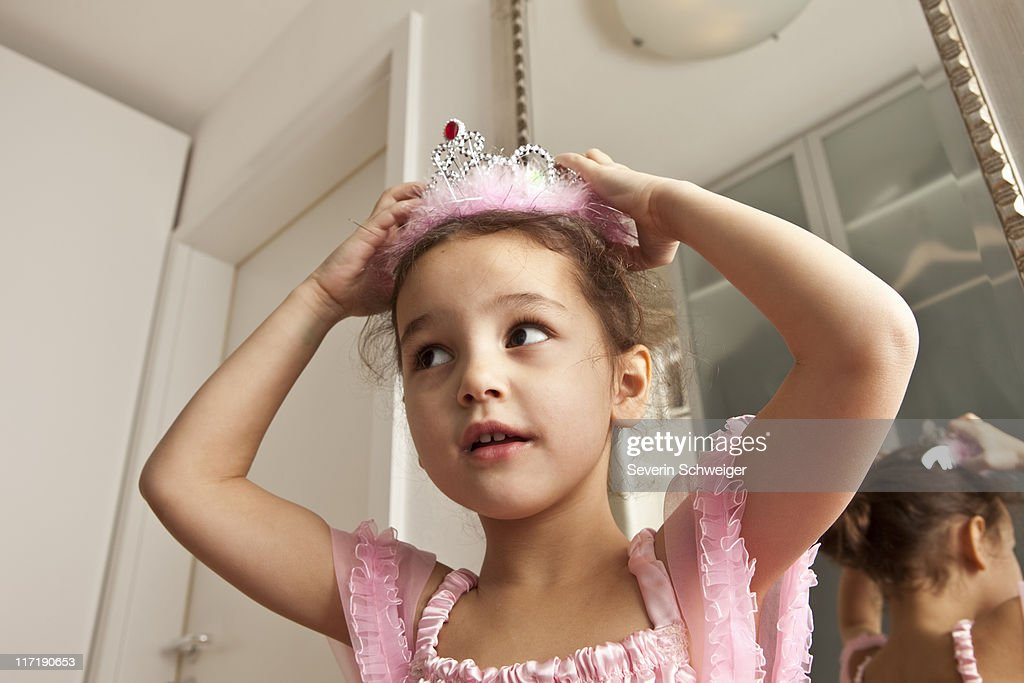 Girl putting crown on her head : Stock Photo