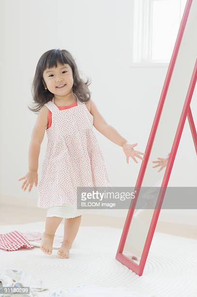 Girl putting dress on in front of mirror