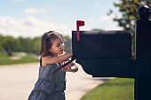 Girl putting letter into mailbox