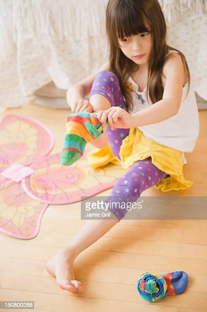 Girl putting on colorful socks