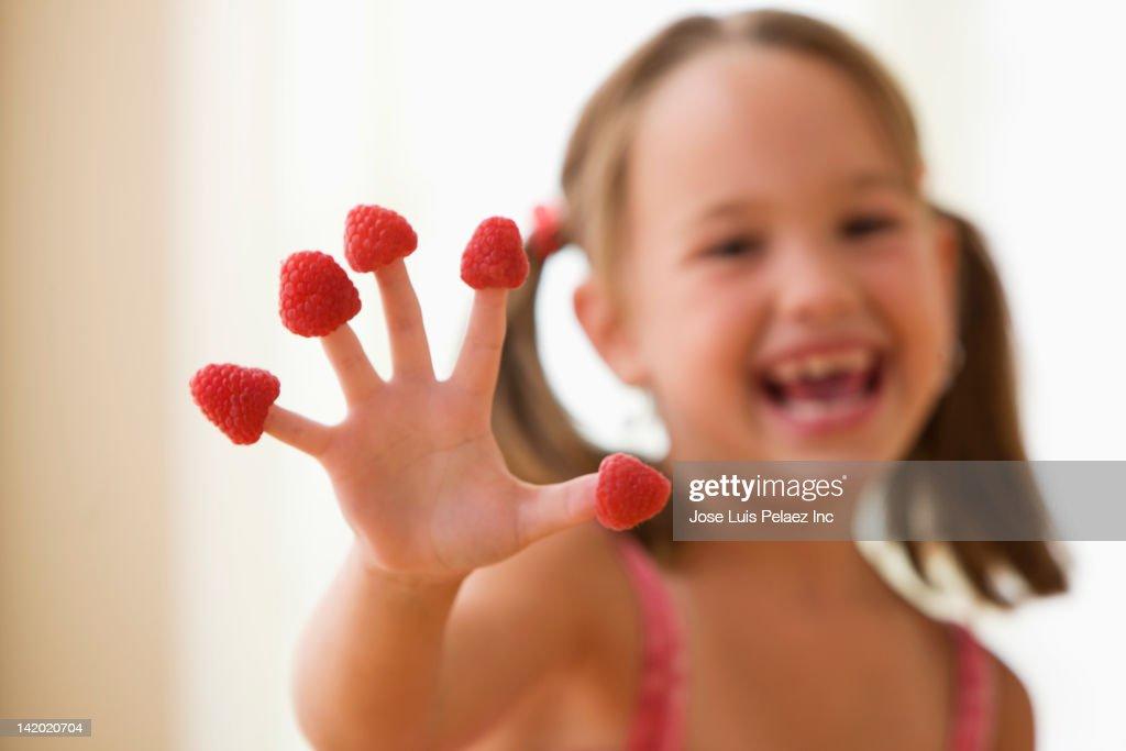 Girl putting raspberries on fingers : Stock Photo