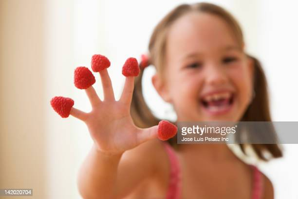 Girl putting raspberries on fingers