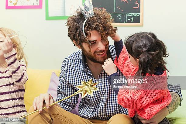girl putting silver crown on dad's head at party
