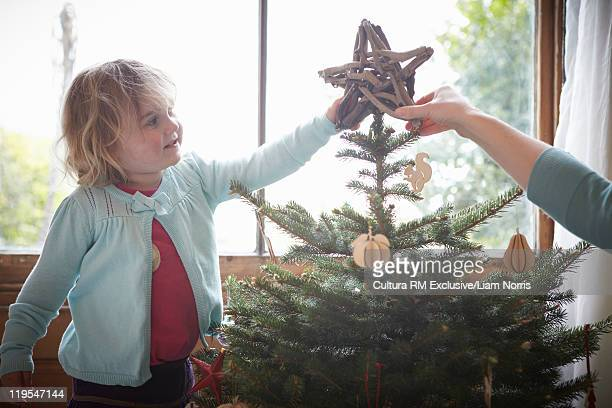 Girl putting star on Christmas tree