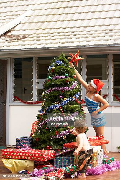 Girl (8-9) putting star on top of Christmas tree on porch with brother (16-18 months)