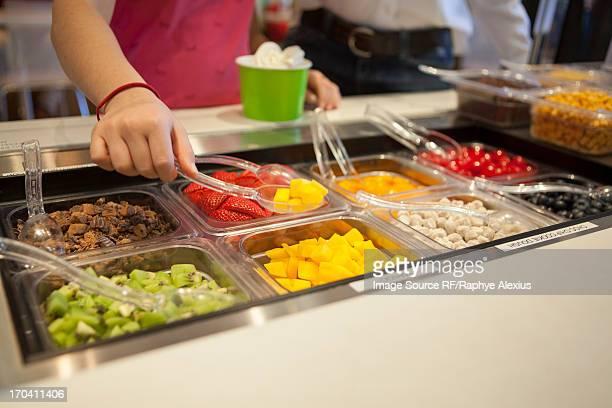 Girl putting toppings on frozen yogurt