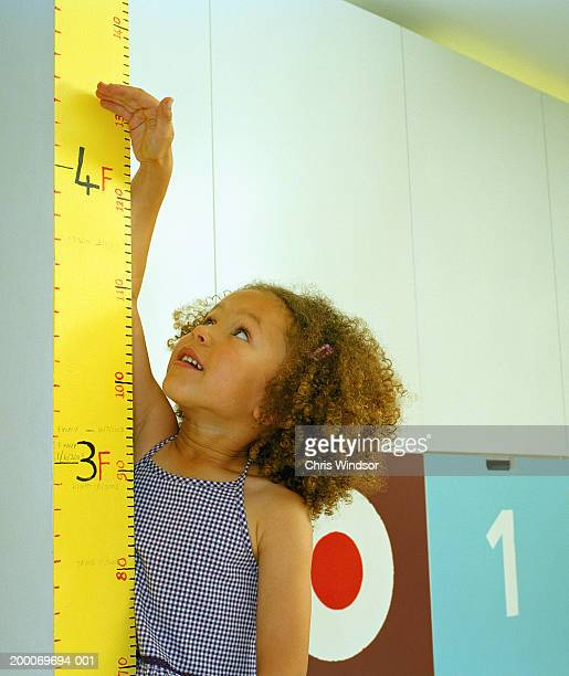 Girl (4-6) raising hand against height chart