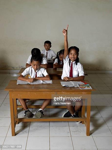 Girl (10-12) raising hand in class, portrait