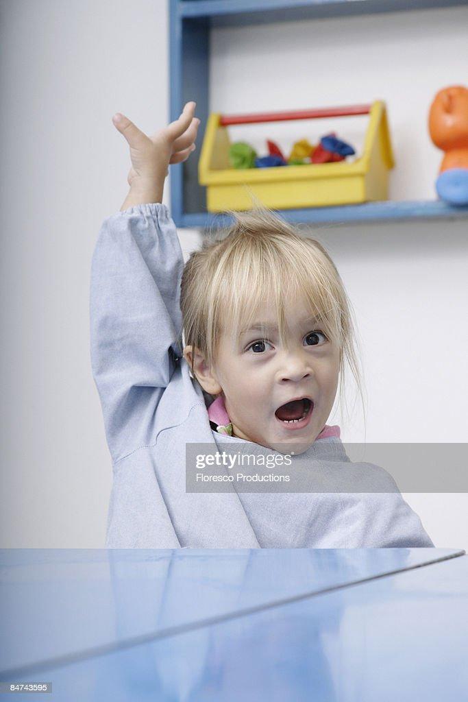 Girl raising hand in classroom : Stock Photo
