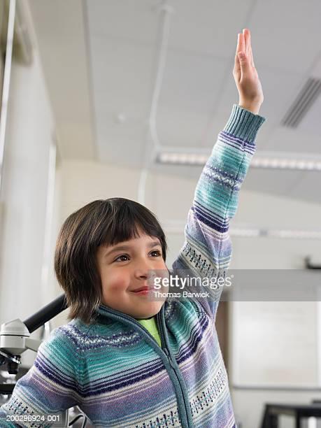 Girl (6-8) raising hand in classroom, smiling