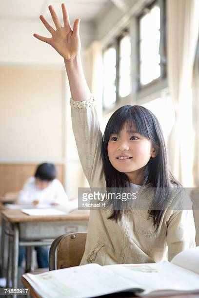 Girl (6-7) raising hand in school classroom
