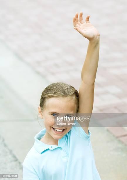 Girl raising hand, smiling